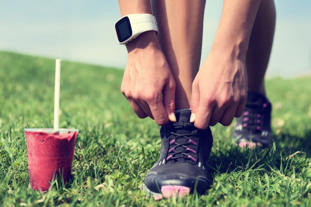 Fresh start on weight loss - runner tying laces with fruit smoot